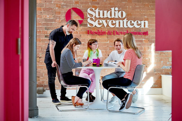 About Studio Seventeen Studio Seventeen group of people sitting at table in front of Studio Seventeen wall)